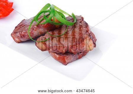 tiras de carne carne assada na chapa de cerâmica branca isolado sobre fundo branco