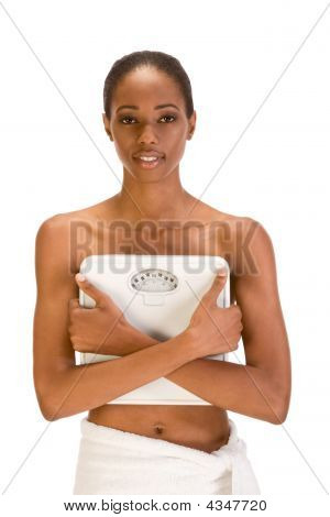 Black Woman Holding Weight Scales In Front Of Her