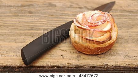 Apple cakes like flower with knife on an old kitchen table.