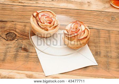 Apple cakes like flower on wooden table