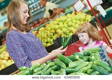woman and little girl choosing cucumbers during shopping at fruit vegetable supermarket