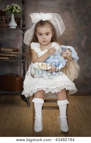 Little Caucasian Girl Is Feeding Her Doll