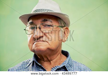 Portrait Of Serious Old Man With Hat Looking At Camera