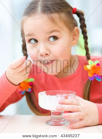 Cute little girl is eating ice-cream in parlor