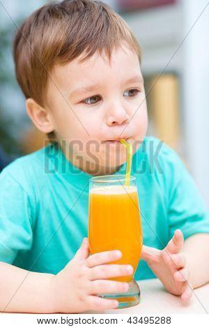 Little boy is drinking orange juice using straw