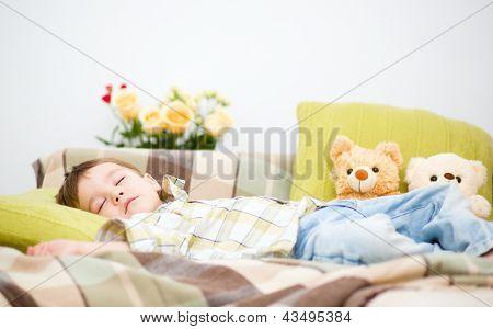 Cute little boy is sleeping next to his teddy bears