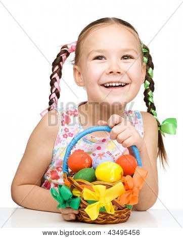 Little girl with basket full of colorful eggs preparing for Easter, isolated over white