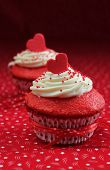 image of red velvet cake  - Red velvet cupcakes with a red heart on top on a red background - JPG