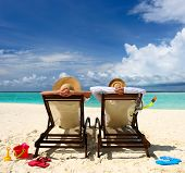 stock photo of couple sitting beach  - Couple on a tropical beach at Maldives - JPG