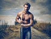 stock photo of rope pulling  - strong handsome man with rope - JPG
