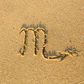Zodiac sign Scorpio, drawn on the facture beach sand. (zodiac signs series)