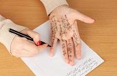 picture of cheating  - Write cheat sheet on hand on wooden table close - JPG