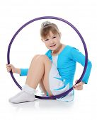 Little girl gymnast does exercise with hoop