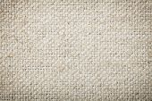 stock photo of canvas  - Background texture of natural unbleached woven canvas or burlap showing fibre and weave texture and pattern with light corner vignetting - JPG