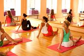 picture of yoga instructor  - Women practicing yoga at health club with instructor - JPG