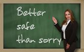 stock photo of saying sorry  - Successful beautiful and confident woman showing Better safe than sorry on blackboard - JPG