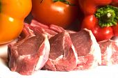 pic of lamb chops  - rib lamb chops raw with red and yellow peppers tomatoes - JPG