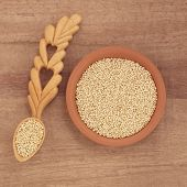 Quinoa grain in a terracotta bowl and wooden spoon over papyrus background.
