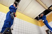 picture of ground nut  - Two electricians repairing ceiling wiring - JPG