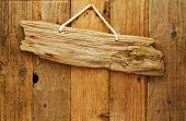 image of driftwood  - old grungy antique wooden plank of driftwood sign on string hung on aged wood door - JPG