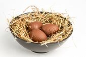 Three chocolate easter eggs in straw in bowl