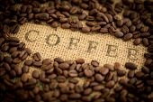 Coffee beans surrounding the word coffee stamped on burlap sack