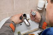 picture of cartridge  - Plumber fixing water tap ceramic cartridge valve in a bathroom - JPG