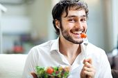 pic of vegetarian meal  - Young man eating a healthy salad - JPG