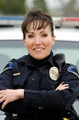 stock photo of lightbar  - a friendly and smiling Hispanic female officer with her patrol car - JPG