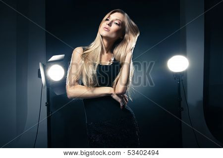 Beautiful woman posing at studio in light flashes