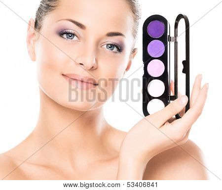 Beauty portrait of young, attractive, fresh, healthy and natural woman with the makeup pallet isolated on white