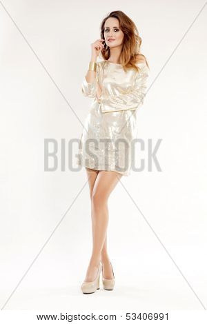 portrait of a beautiful young adult sensuality brunette woman in shiny gold dress carnival creation isolated on white background