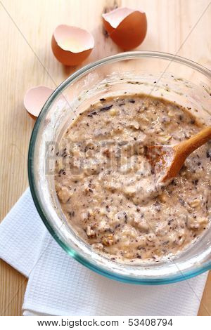 Mix Of Flour, Eggs, Bananas And Chopped Dark Chocolate And Walnuts In Glass Bowl