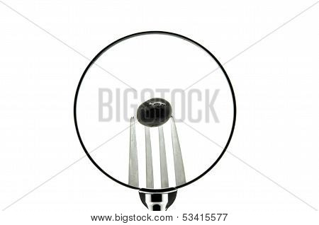 An olive in a fork punctured seen behind a magnifying glass