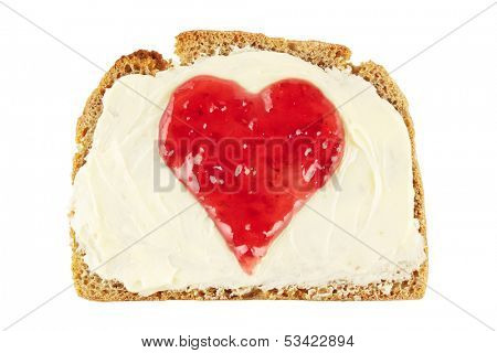 Heart shape made of red jam on a slice of bread with butter