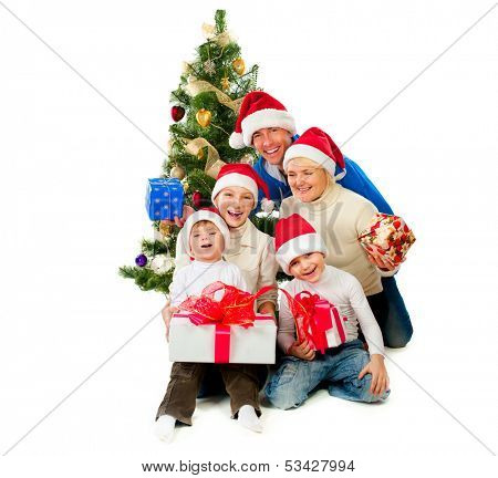 Christmas Family With Gifts near a Christmas Tree isolated on white. Laughing Big Family wearing Santa's Hat - Father, Mother and Kids together. Happy Christmas Holidays