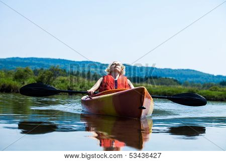 Woman Relaxing On A Kayak And Enjoying Her Life