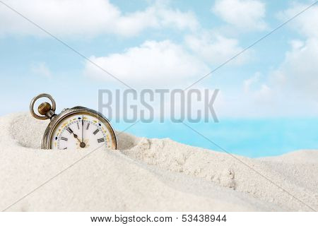 Old beautiful pocket watch lying in the beach sand