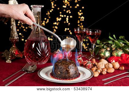 Hand serving burning brandy over a christmas or plum pudding