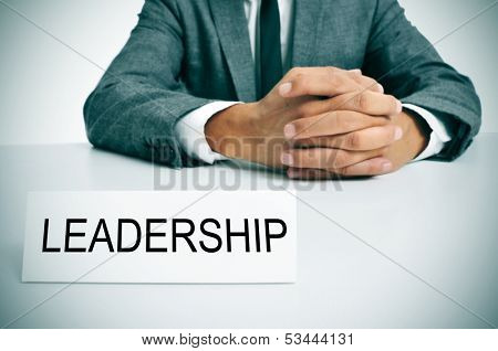 a man wearing a suit sitting in a desk with a signboard in front of him with the word leadership written in it