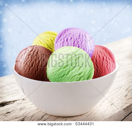 Colorful ice-cream scoops in white cones over snow background.