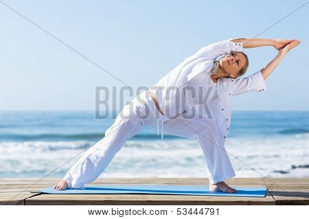 active senior woman yoga exercise on beach