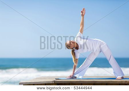 healthy mid age woman practising yoga on beach