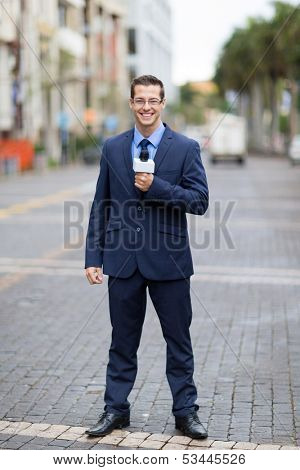 handsome tv journalist reporting from urban street