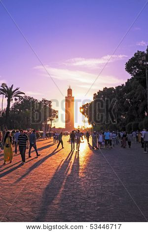 MARRAKESH, MOROCCO - OCTOBER 23: Unidentified people walk at the Jemaa el Fna Square in front of the Koutoubia mosque at sunset on October 23, 2013 in Marrakesh, Morocco.