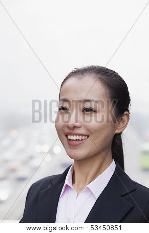 Portrait of young businesswoman looking at camera with traffic below