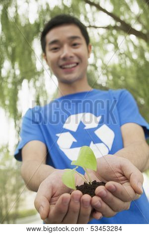 Young man holding seedling in his hands with recycling symbol on his t-shirt