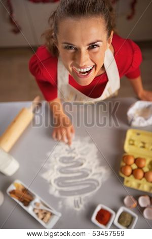 Smiling Young Housewife Drawing Christmas Tree On Kitchen Table