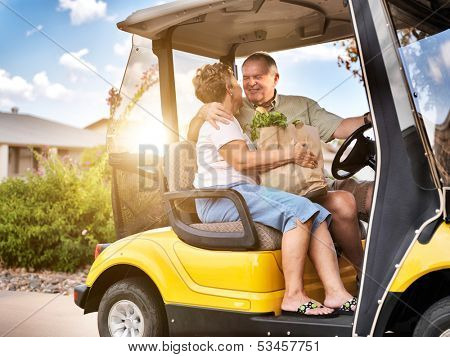 happy elderly couple coming home with groceries on golf cart