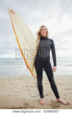 Full length portrait of a smiling young woman in wet suit holding surfboard at beach